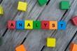 Farbige Holzwürfel mit Buchstaben auf dem das Wort Analyst abgebildet ist, Abstrakte Illustration - 221930117