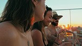 young woman and man people enjoying a beer and the company at a rooftop bar above the city with beautiful view with a cute pet dog - 221936569