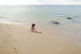 Little girl sitting on sand near sea and playing with doll. Concept of childhood and summer vacations. - 221948777