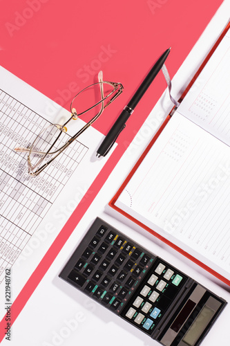 Office table with pen, calculator and glasses. Colour - 221948762