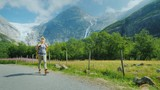 An active successful woman travels through Norway, walks against the backdrop of mountains with a backpack - 221949513