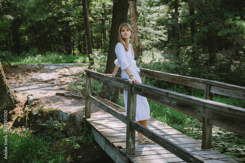 Young woman standing on the wooden bridge in the woods - 221951100