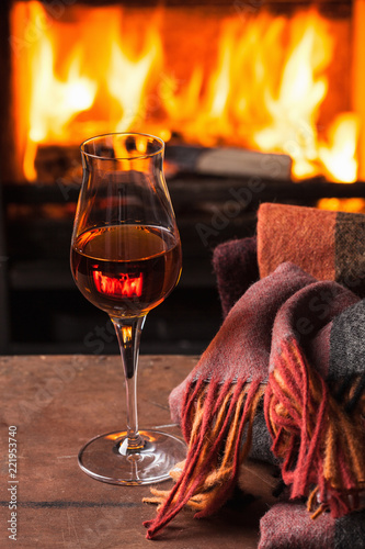 Leinwanddruck Bild a glass of cognac in front of fireplace