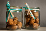 two glass jars filled with whole walnuts decorated with ribbons - 221956120