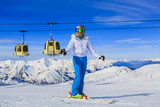 Girl on skiing on snow on a sunny day in the mountains. Ski in winter seasonon, the tops of snowy mountains in sunny day. Meribel resort, 3 vallees, France. - 221961341