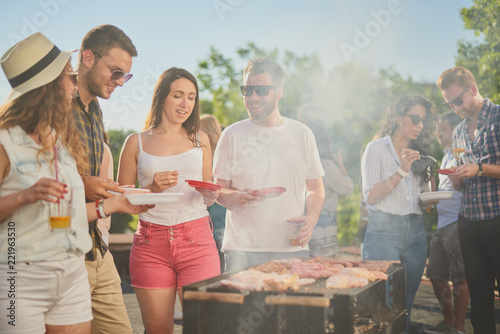 Group of people standing around grill, chatting, drinking and eating.  - 221963530
