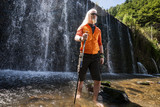 Men with a hiking stick standing in front of a waterfall