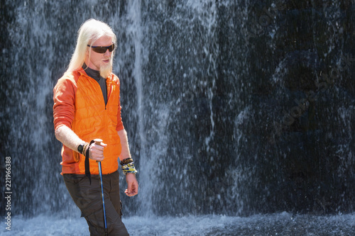 Men with a long blonde hair standing in nature in front of a waterfall - 221966388