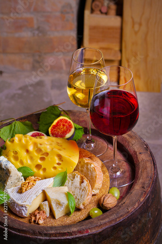 Red and white wine with cheese, grapes, figs and nuts on old cask in wine cellar. Glasses and bottles of wine - 221967109