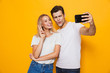 Young loving couple standing isolated over yellow wall background take a selfie by mobile phone.