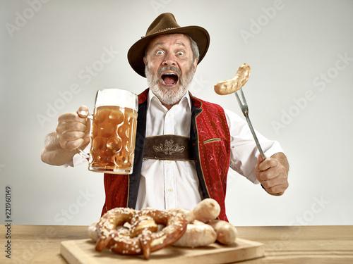 Leinwanddruck Bild Germany, Bavaria, Upper Bavaria. The senior happy smiling man with beer dressed in traditional Austrian or Bavarian costume holding mug of beer at pub or studio. The celebration, oktoberfest, festival