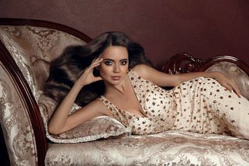 High Fashion brunette woman model in elegant beige dress. Studio portrait of beautiful stunning girl with shine wavy hair style and evening makeup, lying on luxurious sofa in modern interior. © Victoria Andreas