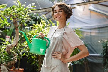 Woman gardener standing over plants in greenhouse water flowers