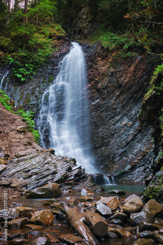Waterfall in mountains with forest. - 221972935