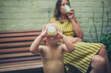 Mother and toddler enjoying drink in yard - 221973131