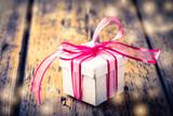 Geschenk mit Schleife auf Holz - 221973355