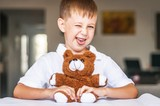 Funny and naughty Caucasian child with a toy teddy bear. Kid showing tongue. Happy childhood concept. - 221973916