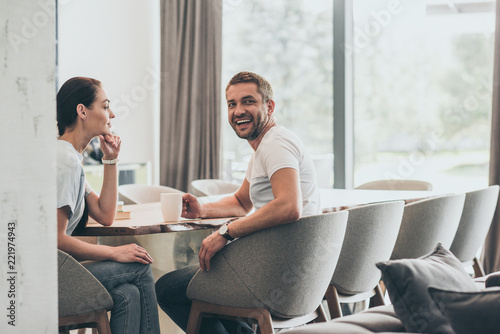 Leinwandbild Motiv laughing adult man with coffee cup sitting at table with girlfriend at home