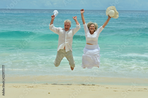 Leinwandbild Motiv Happy elderly couple rest at tropical beach