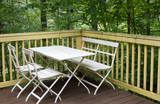 Table with chairs on the veranda in the forest house - 221982353