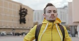 Portrait of young caucasian man wearing yellow stylish jacket in urban city square - 221982524