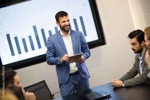 Leinwanddruck Bild Young attractive businessman showing presentation to his colleagues
