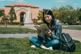 student sitting on ground and reading