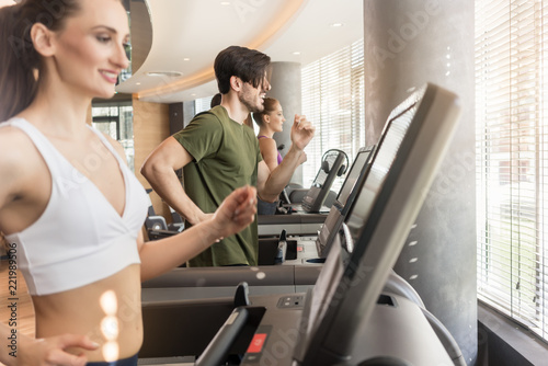 Wall mural Group of four people running on treadmills in fitness gym