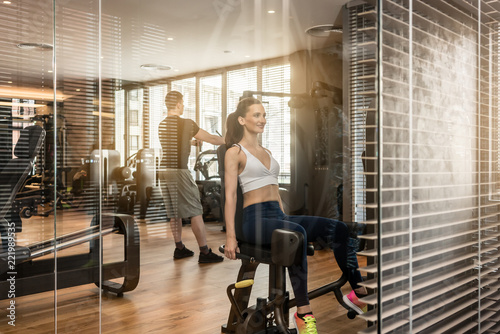 Wall mural Attractive young woman sitting at the abductor machine while exercising for toned buttocks