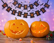 holidays, halloween and decoration concept - close up of pumpkins on table over lights and party garland background