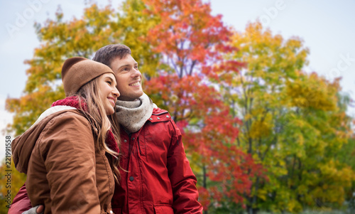 Leinwanddruck Bild love, relationship and season concept - happy teenage couple hugging over autumn park background