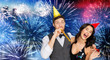 birthday, celebration and holidays concept - happy couple with party blowers and caps having fun over firework background