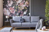 Blanket on grey couch in living room interior with flowers wallpaper and lamp on table. Real photo - 221993789