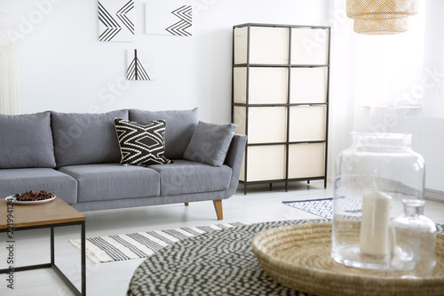 Leinwanddruck Bild Patterned cushion on grey sofa next to screen in modern flat interior with posters. Real photo