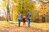 family, season and people concept - happy mother, father and little daughter walking at autumn park