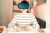 Modern technologies. Young nice woman wearing virtual reality glasses sitting at the table - 222000589
