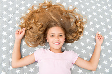 Natural curls treat and care. Girl child with long curly hair lay on bed top view. Child perfect curly hairstyle looks cute. Conditioner mask organic oil keep hair shiny healthy. Amazing curls tips © Roman Stetsyk