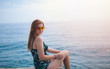 Beautiful young woman sitting on the pier with her back to the sea and enjoying life