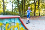 Ein Mädchen skatet auf einem Longboard auf einem städtischen Skatepark