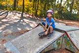 Ein junges Mädchen fährt auf dem Longboard sitzend eine rampe hinunter