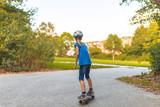 Ein 9 Jahre altes Mädchen skatet auf einem Skateboard auf einem Fahrradweg