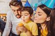 Family time. Vigorous nice family celebrating birthday and gazing at cupcake