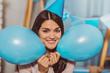 Fun during birthday. Joyful sweet woman holding balloons while grinning to camera