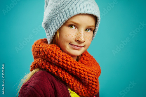 7606a38af1b Close up studio portrait of beautiful child girl wearing a round scarf  orange and blue winter