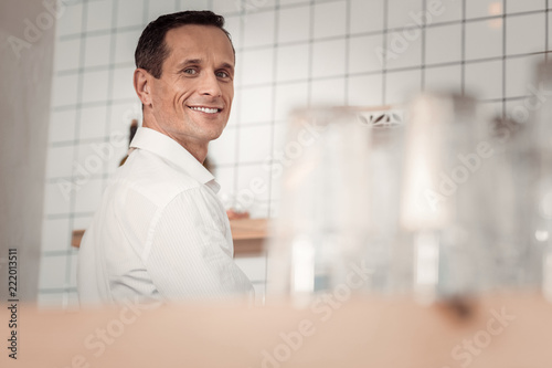 My workplace. Cheerful positive man standing near the coffee machine while being at work - 222013511