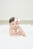 Baby girl smiling on the floor isolated on white - 222014592