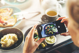 woman with smart phone taking picture of food at restaurant - 222016373