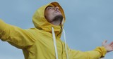 Man in yellow jacket with raised hands enjoy overcast cloudy weather sky background - 222029533
