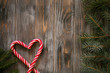 festive minimalistic holiday decor background. seasonal design with fir tree branch and candy cane in heart shape on grey wooden backdrop with free space.