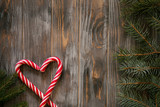 festive minimalistic holiday decor background. seasonal design with fir tree branch and candy cane in heart shape on grey wooden backdrop with free space. - 222030511